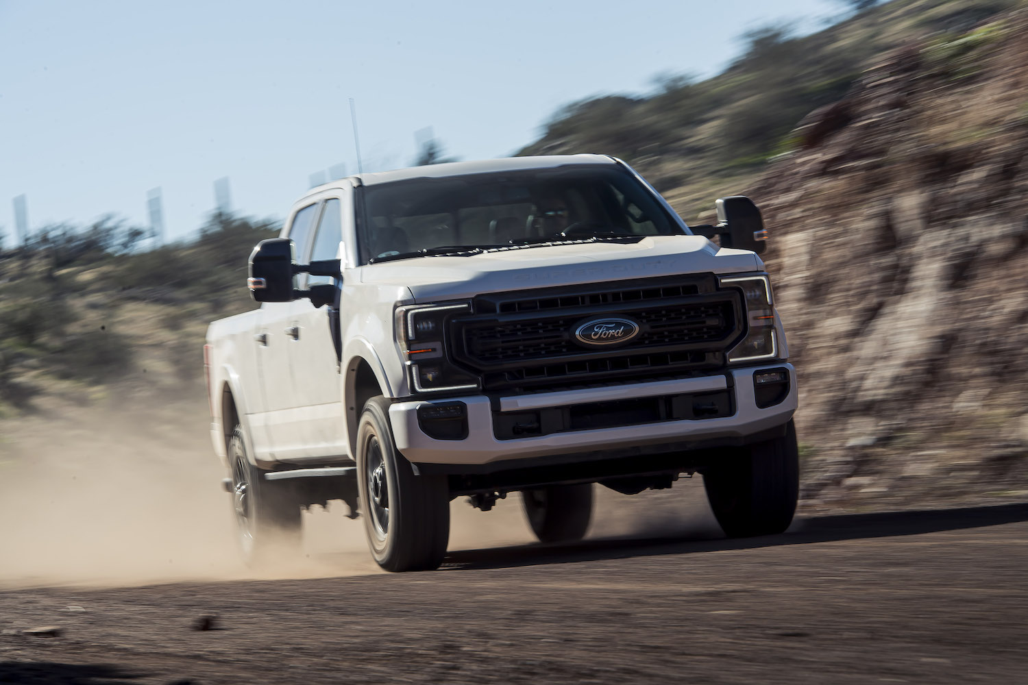 ford super duty front three-quarter on dirt road action
