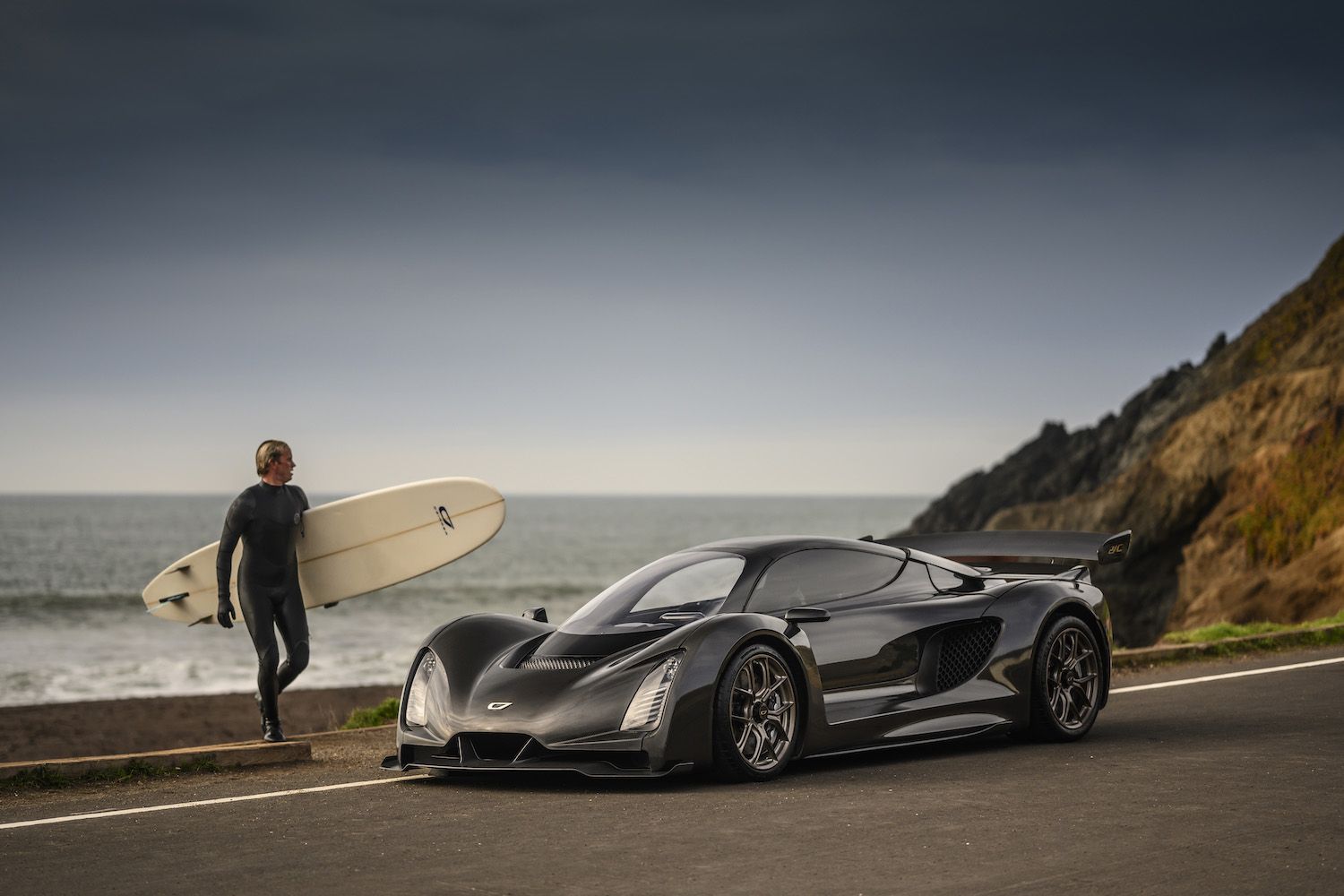 Czinger 21C 3D print hybrid supercar front three-quarter and surfer on pacific coast highway