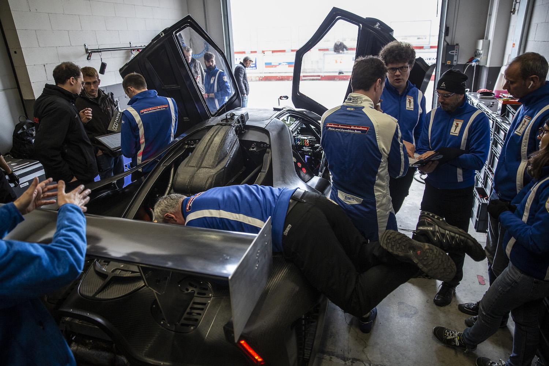 SCG 004 crew working on car