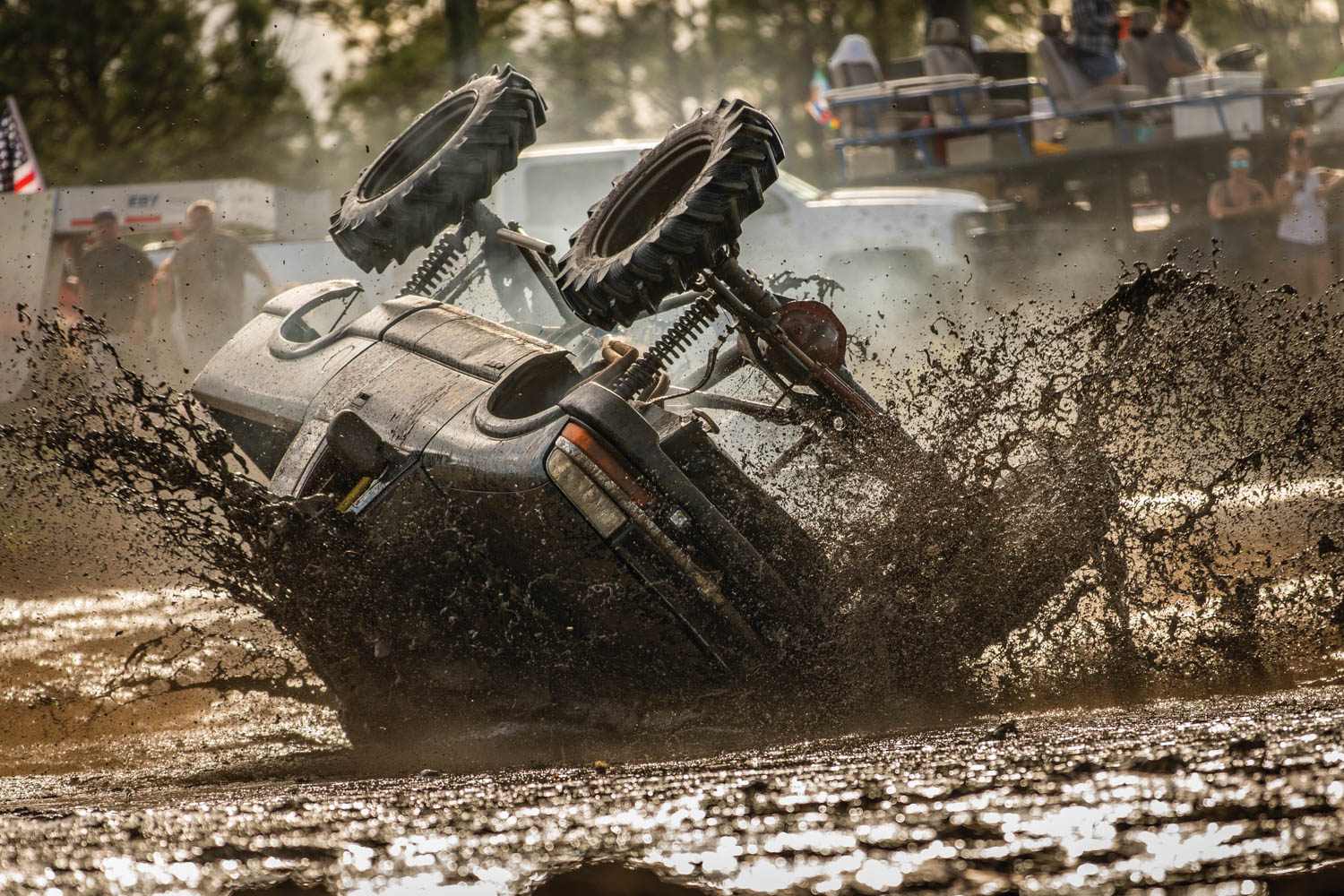 Wrecking is racing. A mud racer catches a rut and topples over in the slurry.