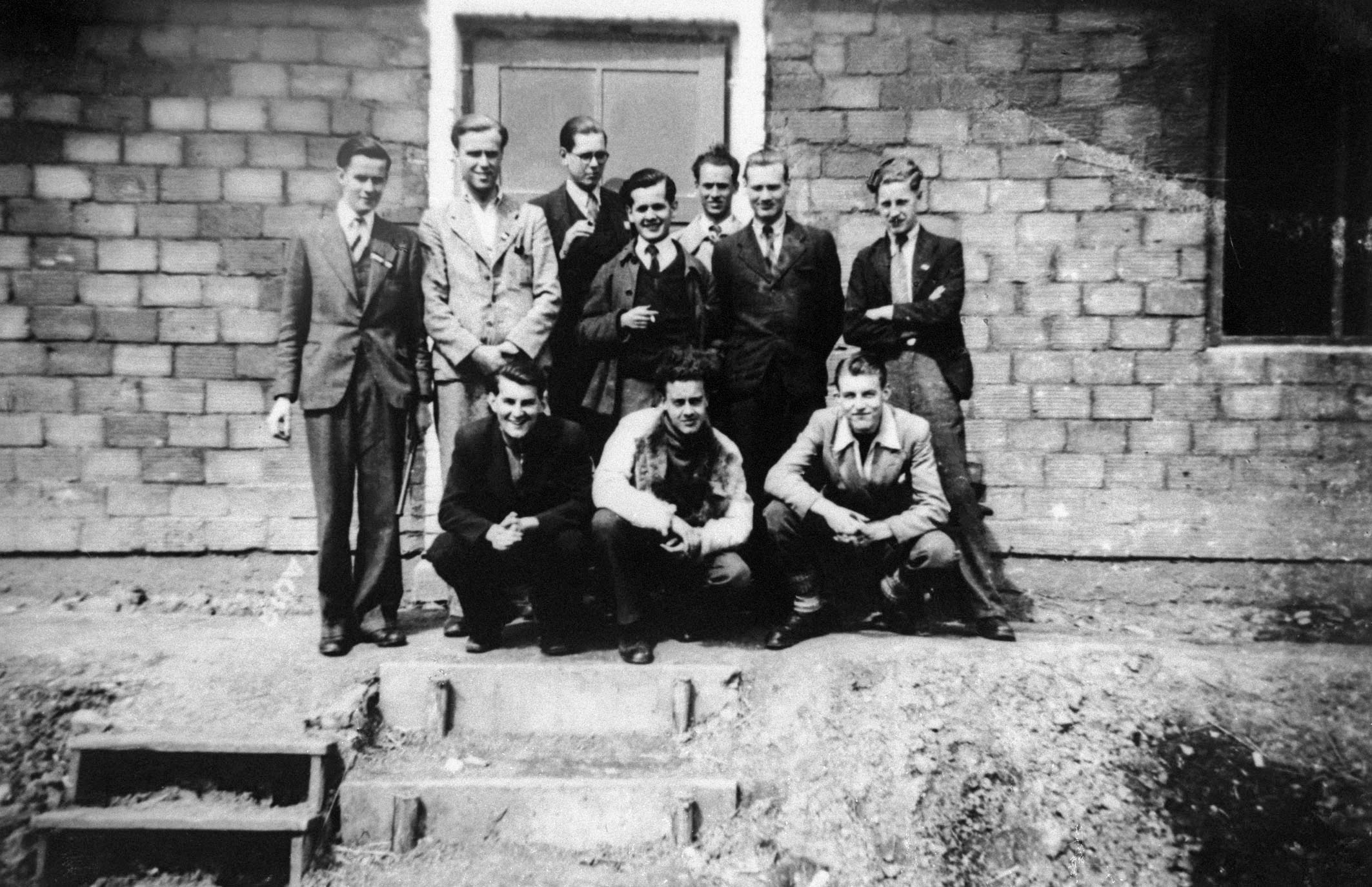 Dutch Students in front of their barrack hut at the workers' camp.