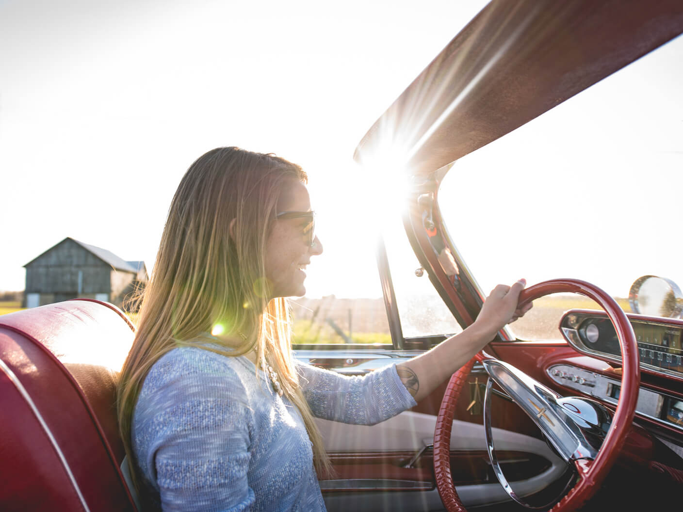 Bright sunshine beams down on a woman happily driving a red convertible.