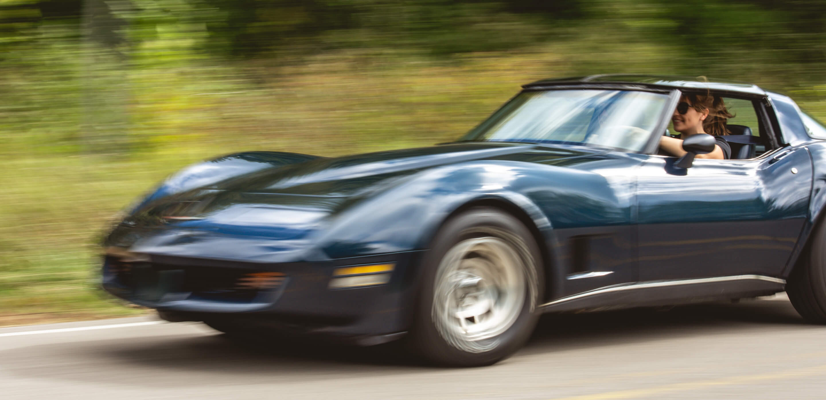 A black collector Corvette being driven down a country road by a woman wearing sunglasses.