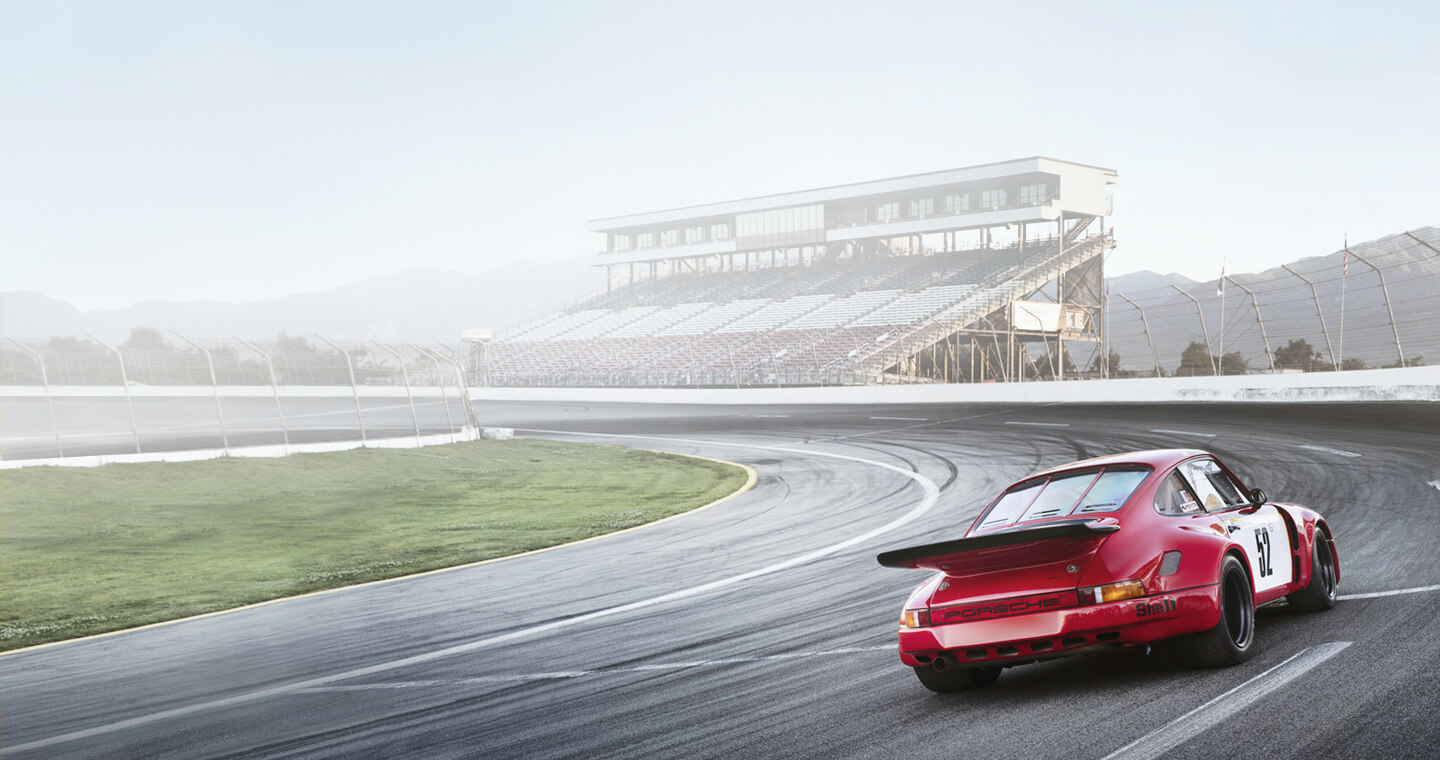 A red collector race car driving solo on a race track, with audience stands in the background.