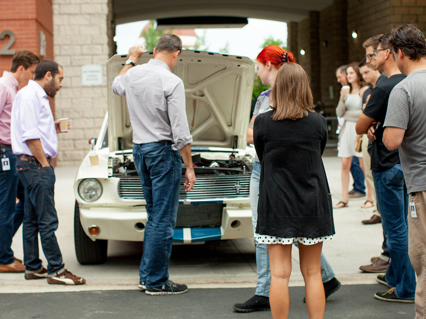 A group of collector car enthusiasts gather around a white Mustang with the hood popped up.