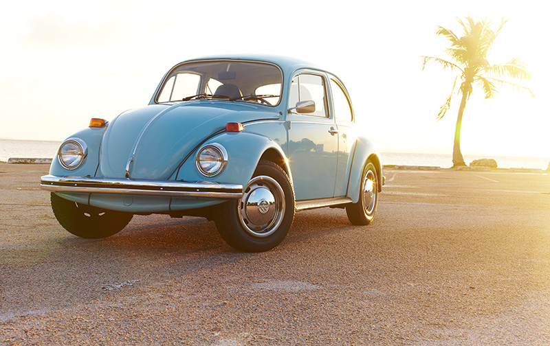 Light blue classic Volkswagen Beetle driving in foreground, palm trees in background