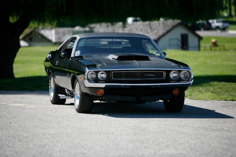Black Challenger parked facing straight on with trees in background