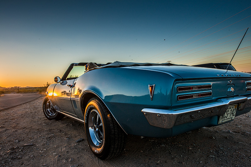 Back three-quarter view of classic Pontiac Firebird convertible directed at the sunset in background